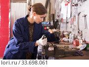 Young woman handles part on bench vise. Стоковое фото, фотограф Яков Филимонов / Фотобанк Лори