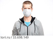 Купить «A sports confident wounded man with a medical mask and a Band-Aid on his head from the injury, sportswear, smiling, looking at the camera. Isolated», фото № 33698149, снято 23 апреля 2020 г. (c) Владимир Арсентьев / Фотобанк Лори
