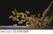 Купить «Female's hands are throwing fresh homemade raw pasta from glass bowl on a dark wooden table on a black background. Slow motion, Full HD video, 240fps, 1080p.», видеоролик № 33699665, снято 31 августа 2018 г. (c) Ярослав Данильченко / Фотобанк Лори