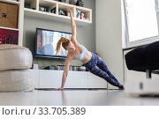Купить «Attractive sporty woman working out at home, doing pilates exercise in front of television in her living room. Social distancing. Stay healthy and stay at home during corona virus pandemic», фото № 33705389, снято 8 апреля 2020 г. (c) Matej Kastelic / Фотобанк Лори