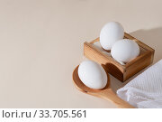 Chicken eggs in a wooden box on beige background with copy space, product with amino acids choline lecithin cholesterol calcium potassium phosphorus magnesium iodine protein vitamins healthy diet food. Стоковое фото, фотограф Светлана Евграфова / Фотобанк Лори