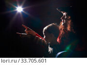 Ugle oman in red sweater and pirate hat with curly hair posing with small boy on black background. Actress mother and actor son in magical, fantastic, fairy-tale movie in dark studio and flash. Стоковое фото, фотограф Кривошеина Елена Леонидовна / Фотобанк Лори