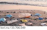 Купить «Disposable face masks and plastic debris on the beach in surf zone. Coronavirus COVID-19 is contributing to pollution, as discarded used masks clutter polluting urban beaches along with plastic trash», видеоролик № 33706049, снято 5 апреля 2020 г. (c) Некрасов Андрей / Фотобанк Лори