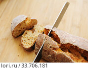 Sliced white yeast-free curd wheat bread on wooden board. Bread knife. Стоковое фото, фотограф Кристина Сорокина / Фотобанк Лори