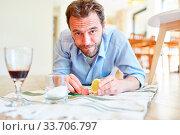 Hausmann als Putzmann beim entfernen von Rotweinflecken mit Zitrone und Salz. Стоковое фото, фотограф Zoonar.com/Robert Kneschke / age Fotostock / Фотобанк Лори