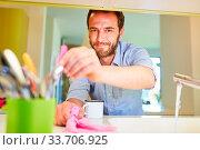Купить «Mann als Hausmann beim putzen in der Küche als Konzept für Rollentausch», фото № 33706925, снято 26 мая 2020 г. (c) age Fotostock / Фотобанк Лори