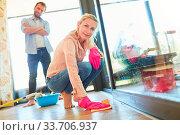 Купить «Mann beobachtet Hausfrau beim Fußboden putzen als Konzept für Rollenverteilung», фото № 33706937, снято 26 мая 2020 г. (c) age Fotostock / Фотобанк Лори