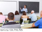 Купить «Confident lecturer talking to mixed age students», фото № 33710705, снято 28 июня 2018 г. (c) Яков Филимонов / Фотобанк Лори