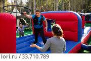 People passing obstacles on inflatable arena at amusement park. Стоковое фото, фотограф Яков Филимонов / Фотобанк Лори