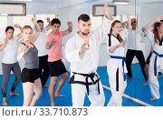 Adults trying new martial moves at karate class. Стоковое фото, фотограф Яков Филимонов / Фотобанк Лори