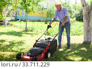 Купить «Positive elderly man with lawnmower when mowing the lawn», фото № 33711229, снято 25 июня 2019 г. (c) Татьяна Яцевич / Фотобанк Лори