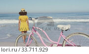 Купить «African American woman walking seaside with a bike in foreground», видеоролик № 33711929, снято 25 февраля 2020 г. (c) Wavebreak Media / Фотобанк Лори