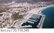 Купить «Picturesque aerial view of Mediterranean coastal town of Torredembarra with yachts moored in harbor, Tarragona, Spain», видеоролик № 33716345, снято 18 марта 2019 г. (c) Яков Филимонов / Фотобанк Лори