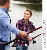 Boy fishing with man on freshwater lake on forest. Стоковое фото, фотограф Яков Филимонов / Фотобанк Лори