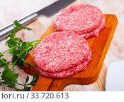 Close up of raw burger cutlet from pork on wooden table. Стоковое фото, фотограф Яков Филимонов / Фотобанк Лори
