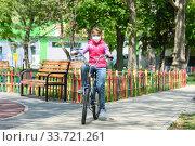 Купить «Десятилетняя девочка в медицинской защитной маске катается на велосипеде», фото № 33721261, снято 2 мая 2020 г. (c) Иванов Алексей / Фотобанк Лори