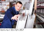 Купить «Production worker with PVC windows», фото № 33721357, снято 30 марта 2017 г. (c) Яков Филимонов / Фотобанк Лори