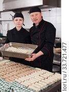 Купить «Two cooks holding baking tray with cannelloni», фото № 33721477, снято 11 апреля 2019 г. (c) Яков Филимонов / Фотобанк Лори