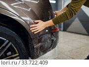Купить «Worker applies car protection film on rear bumper», фото № 33722409, снято 20 марта 2020 г. (c) Tryapitsyn Sergiy / Фотобанк Лори