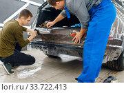 Купить «Specialists applies car protection film on bumper», фото № 33722413, снято 20 марта 2020 г. (c) Tryapitsyn Sergiy / Фотобанк Лори