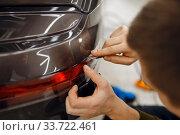 Купить «Specialist cuts car protection film on bumper», фото № 33722461, снято 20 марта 2020 г. (c) Tryapitsyn Sergiy / Фотобанк Лори