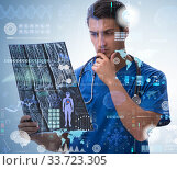 Young doctor looking at x-ray image in mhealth concept. Стоковое фото, фотограф Elnur / Фотобанк Лори