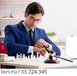 Купить «Young lawyer playing chess to train his court strategy and tacti», фото № 33724345, снято 31 июля 2018 г. (c) Elnur / Фотобанк Лори