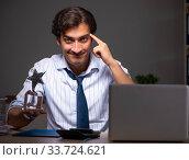 Купить «Young financial manager working late at night in office», фото № 33724621, снято 25 июля 2018 г. (c) Elnur / Фотобанк Лори