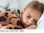 Купить «Девочка неспешно просыпается, лежа в кровати и накрывшись старым одеялом», фото № 33727185, снято 9 мая 2020 г. (c) Иванов Алексей / Фотобанк Лори