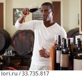 Купить «Confident african american male winemaker inspecting quality of red wine, checking it in wine store», фото № 33735817, снято 1 августа 2019 г. (c) Яков Филимонов / Фотобанк Лори
