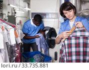 Woman dry cleaning clothes in laundry. Стоковое фото, фотограф Яков Филимонов / Фотобанк Лори