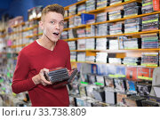 Surprised young guy standing in shop with stack of DVDs. Стоковое фото, фотограф Яков Филимонов / Фотобанк Лори