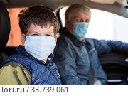 Preteen age boy sitting on passenger seat with his father as driver, men wearing surgical masks against coronavirus, looking at camera. Стоковое фото, фотограф Кекяляйнен Андрей / Фотобанк Лори