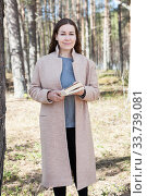 Portrait of Caucasian woman holding the book in hands, beige coat, sunny spring forest. Стоковое фото, фотограф Кекяляйнен Андрей / Фотобанк Лори