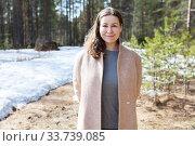 Attractive young woman wearing beige coat standing in spring forest, portrait. Стоковое фото, фотограф Кекяляйнен Андрей / Фотобанк Лори