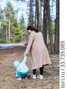 Купить «Rear view at mother with her toddler child walk together in spring park», фото № 33739089, снято 7 мая 2020 г. (c) Кекяляйнен Андрей / Фотобанк Лори