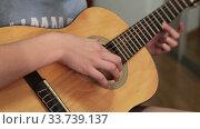 Купить «Teenager girl slams on her acoustic guitar, unrecognizable person», видеоролик № 33739137, снято 2 марта 2020 г. (c) Кекяляйнен Андрей / Фотобанк Лори