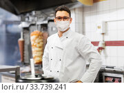 male chef with in face mask at kebab shop kitchen. Стоковое фото, фотограф Syda Productions / Фотобанк Лори