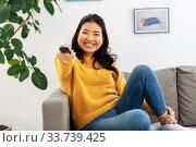 Купить «asian woman with tv remote sitting on sofa at home», фото № 33739425, снято 14 марта 2020 г. (c) Syda Productions / Фотобанк Лори