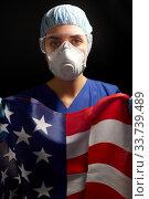 Купить «doctor in goggles and mask holding flag of america», фото № 33739489, снято 2 апреля 2020 г. (c) Syda Productions / Фотобанк Лори