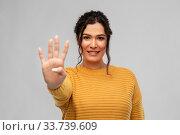 Купить «happy woman in pullover showing four fingers», фото № 33739609, снято 20 марта 2020 г. (c) Syda Productions / Фотобанк Лори