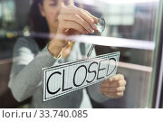 woman hanging banner with closed word on door. Стоковое фото, фотограф Syda Productions / Фотобанк Лори