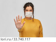 Купить «woman in medical mask making stop gesture», фото № 33740117, снято 20 марта 2020 г. (c) Syda Productions / Фотобанк Лори