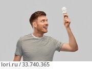 Купить «smiling young man holding lighting bulb», фото № 33740365, снято 21 марта 2020 г. (c) Syda Productions / Фотобанк Лори