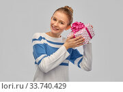 smiling teenage girl in pullover with gift box. Стоковое фото, фотограф Syda Productions / Фотобанк Лори