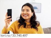 Купить «asian woman with earphones and smartphone at home», фото № 33740497, снято 14 марта 2020 г. (c) Syda Productions / Фотобанк Лори