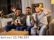Купить «friends or soccer fans with ball and beer at home», фото № 33740501, снято 28 декабря 2019 г. (c) Syda Productions / Фотобанк Лори