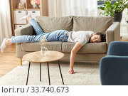 bored or lazy young woman lying on sofa at home. Стоковое фото, фотограф Syda Productions / Фотобанк Лори