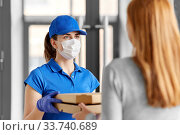 delivery girl in mask giving pizza boxes to woman. Стоковое фото, фотограф Syda Productions / Фотобанк Лори