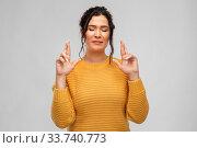 Купить «woman with pierced nose holding fingers crossed», фото № 33740773, снято 20 марта 2020 г. (c) Syda Productions / Фотобанк Лори